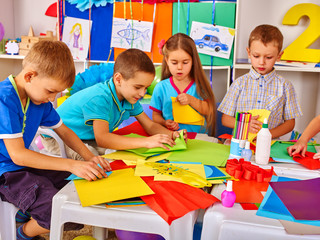 Children are making something out of colored paper on table in primary school. Children craft lesson in primary school. Development children craft at class in school.