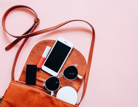 Flat lay of brown leather woman bag open out with cosmetics, acc