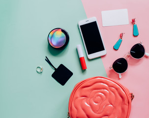 Flat lay of pink cute woman bag open out with cosmetics, accesso