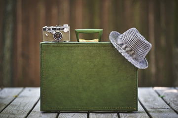 a vintage suitcase, camera, and hat