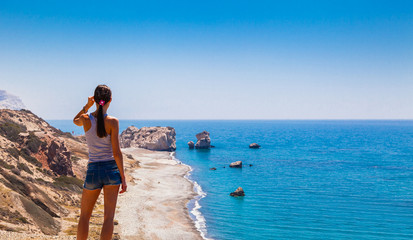 Garden Poster Cyprus Woman looks on panoramic landscape Petra tou Romiou (The rock of the Greek), Aphrodite's legendary birthplace in Paphos, Cyprus island, Mediterranean Sea. Amazing blue green sea and sunny day.