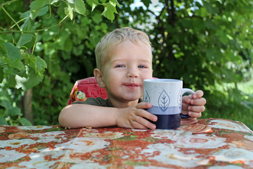 Small white boy drinks juice from a cup. Traces of juice on the