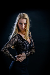 blonde girl on a black background in a dark guipure dress