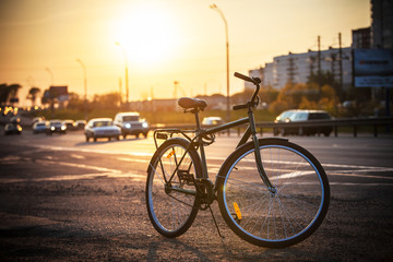 Classic city bike on the road at sunset