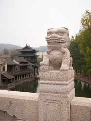 Statue of Chinese dragon on a background of the temple with water and trees