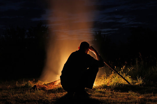 Silhouette of a man with a long stick sitting by the fire at nig