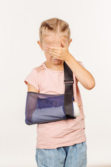 Crying girl with broken arm  is standing and covering her face