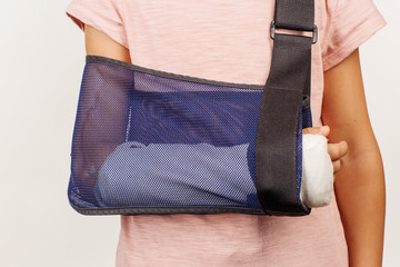 Girl's broken arm in a bandage. Concept of this photo is medicin