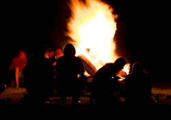 silhouette of people sitting in front of a campfire in the night