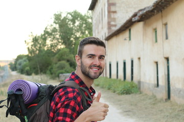 A portrait of a man with backpack giving thumb up isolated on stunning European countryside background with copy space