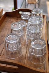 Water glasses stacked on a rustic wooden tray at a cafe. Photographed in New Zealand NZ.
