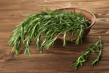 Fresh rosemary in bowl on wooden table