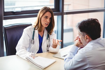 Female doctor sitting at her desk talking to patient