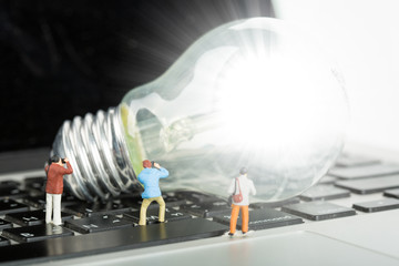 Photographer found creativity ideas concept with human miniature, light bulb on a keyboard