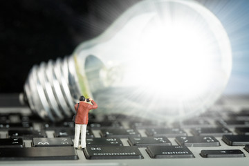 Photographer found creativity ideas concept with human miniature, light bulb on a keyboard