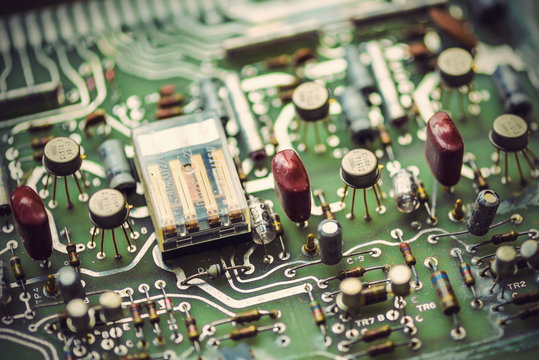 old printed circuit board with electronic components, vintage filtered style
