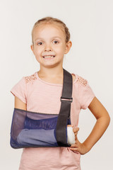 Smiling  girl with broken arm  is standing and looking at the camera