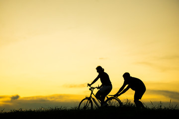 sillhouette of man teaching woman to ride bicycle with vintage bicycle at sunset time.