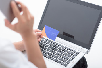 Close up of hands holding credit card and smart phone . People using laptop for online payment.