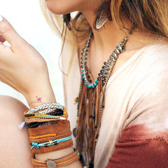 Female neck and hands with many boho bracelets, leather necklace and earrings with feathers
