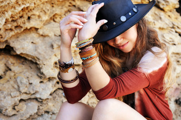 Female hands with boho chic bracelets holding black hat