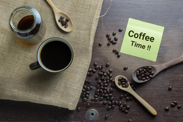 Coffee cup, coffee beans on wooden table with note paper.