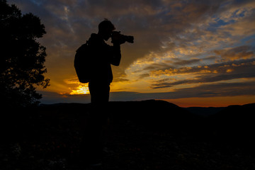 silhouette of photographer taking picture of landscape during su