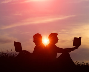 silhouette of a men with laptop and a book on sunset or sunrise background