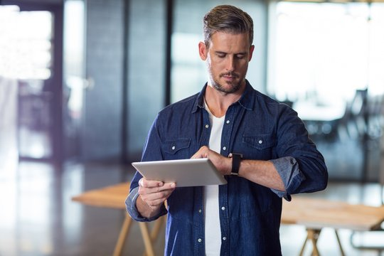 Man checking time while holding tablet