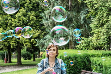 Young caucasian woman blowing soap bubbles in the city park