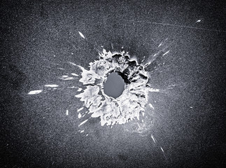 Bullet hole in the metal plate, black and white photo