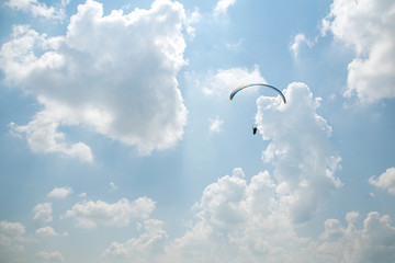 Paraglider in the blue sky, big blue clouds