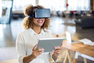 Woman wearing virtual reality glass with digital tablet