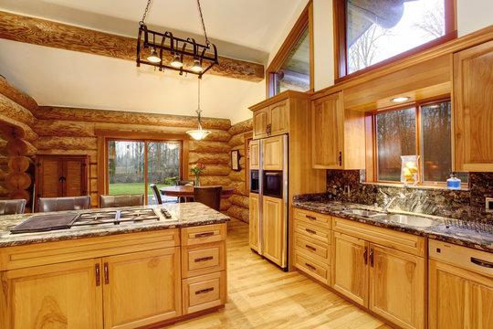 Log cabin kitchen interior design with honey color cabinets.