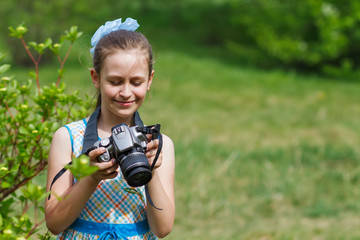 Small girl taking pictures in green field