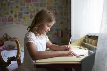 Young Girl Sitting At Desk And Writing In Bedroom