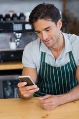 Smiling waiter using mobile phone