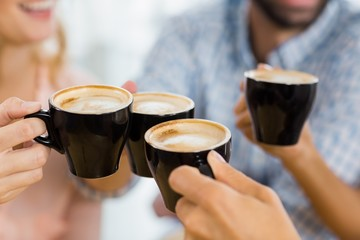 Group of happy friends toasting cup of coffee