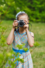 A girl taking picture in green bushes