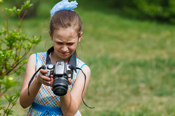 A child girl taking pictures at a meadow