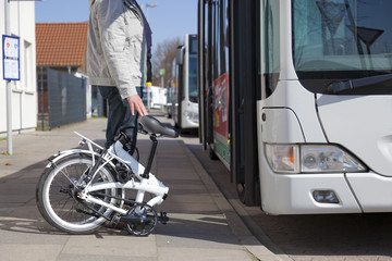 Germany, Wunstdorf, bus station, man with folding bicycle in front of bus