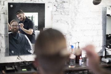 Barber and customer, barber combs his hair