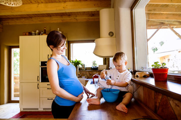 Little boy helping his pregnant mother in kitchen with electric whisker