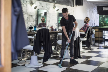 Barber sweeping in barber's shop