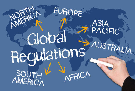 Global Regulations - blue chalkboard with world map and female hand