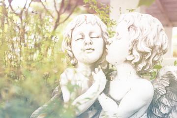 Angel Cupid ,White plaster figurine in the garden