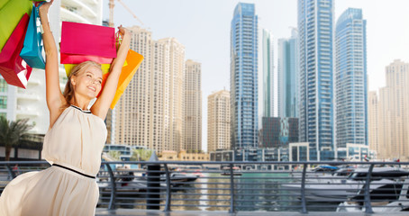 happy woman with shopping bags over dubai city