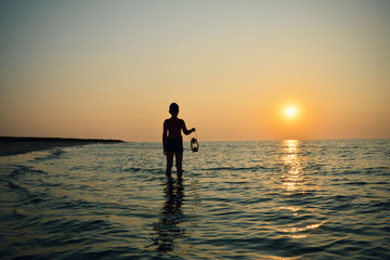 Young boy with lamp at sunrise on the beach