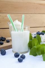 Glass of fresh milk with drinking straw on the table with other dairy products, bilberry and fresh mint
