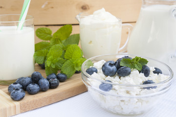 Culinary cottage cheese with bilberry and fresh mint in a class bowl on the table with other dairy products